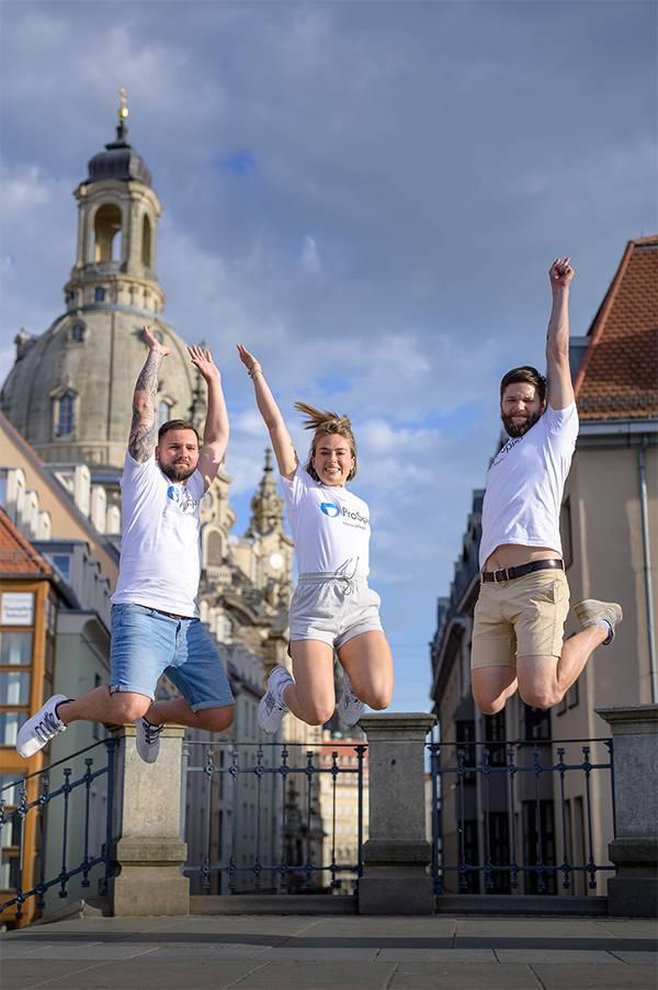 3 Pflegefachkräfte springen in die Luft vor der Frauenkirche Dresden